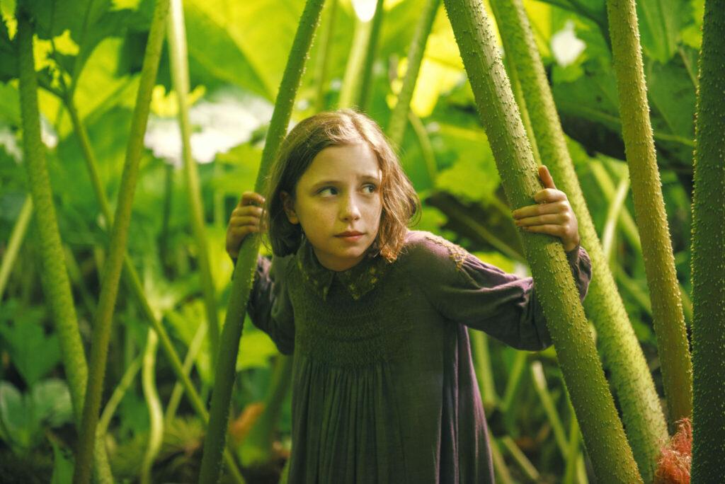 Mary, gespielt von Dixie Egerickx, steht zwischen riesigen und sich bewegenden Farnen.