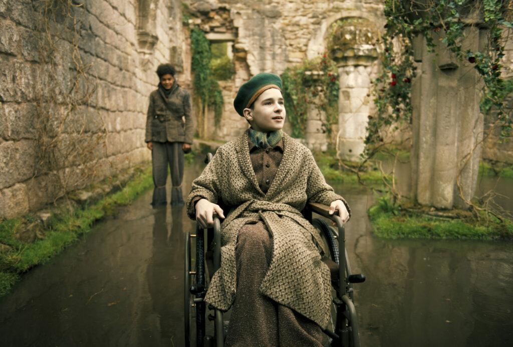 Colin, gespielt von Edan Hayhurst, sitzt in seinem Rollstuhl zwischen den antik anmutenden Tempelruinen im geheimen Garten. Hinter ihm steht Dickon, gespielt von Amir Wilson.