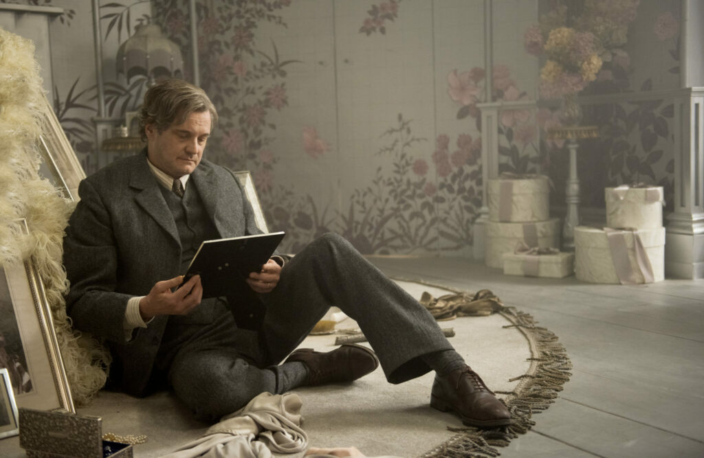 Lord Archibald Craven, gespielt von Colin Firth, sitzt verzweifelt auf dem Boden im Zimmer seiner verstorbenen Frau und betrachtet ein ates Foto von ihr.