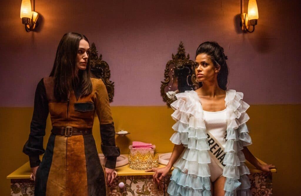 In der Toilette trifft Sally Alexander, gespielt von Keira Knightley, auf Miss Grenada, gespielt von Gugu Mbatha-Raw in Die Misswahl - Der Beginn einer Revolution.