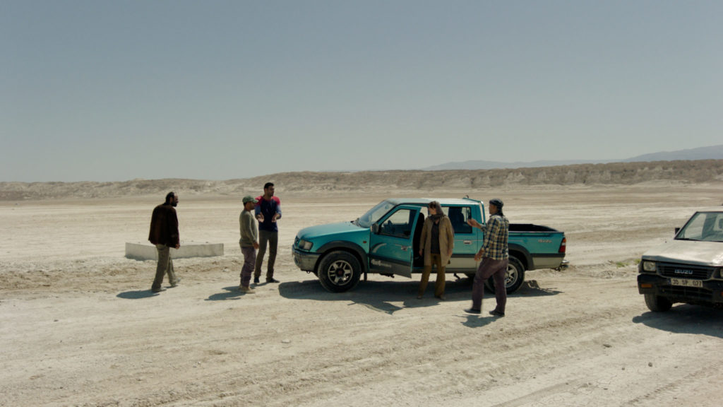 Die Agentin Rachel, gespielt von Diane Kruger, steht in der Bildmitte an der Fahrertür eines Geländewagens in der Wüste, von verbündeten Agenten umgeben. Um Sprengstoff von der Türkei in den Iran zu schmuggeln, muss sie sich mit zweifelhaften Gesellen einlassen.