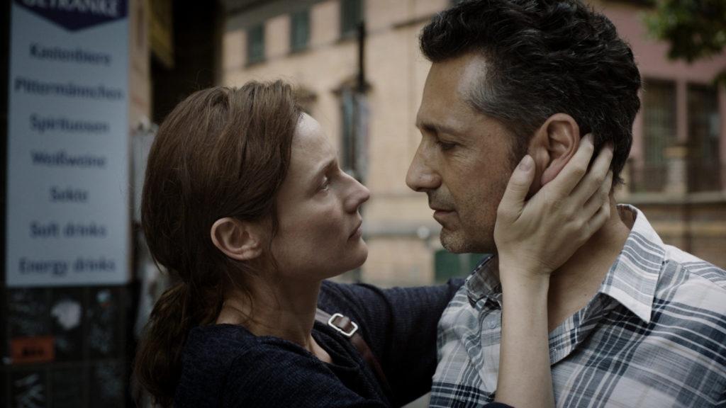 Auf Farhad Razavi, gespielt von Cas Anvar angesetzt, verliebt sich Rachel, gespielt von Diane Kruger, als Die Agentin in den charismatischen Geschäftsmann. Auf dem Bild stehen sich beide gegenüber. Die links stehende Rachel umfasst Farhads Kopf mit beiden Händen.