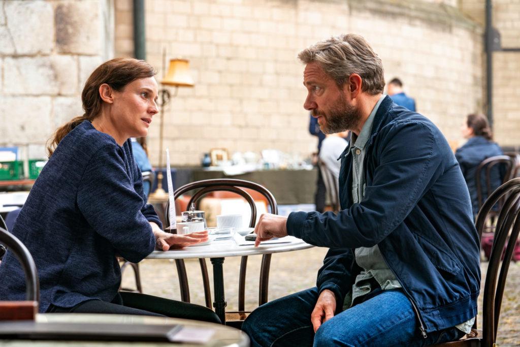 Rachel, gespielt von Dianae Kruger, sitzt in Die Agentin links am Tisch eines Straßencafés. Ihr gegenüber sitzt Thomas, gespielt von Martin Freeman. Beide sind in einem Krisengespräch vertieft.