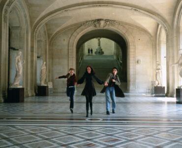 Isabelle (Eva Green), Matthew (Michael Pitt) und Theo (Louis Garrel) sprinten in Die Träumer Hand in Hand durch das Louvre, um den Geschwindigkeitsrekord aus Jean-Luc Godards Die Außenseiterbande zu knacken.
