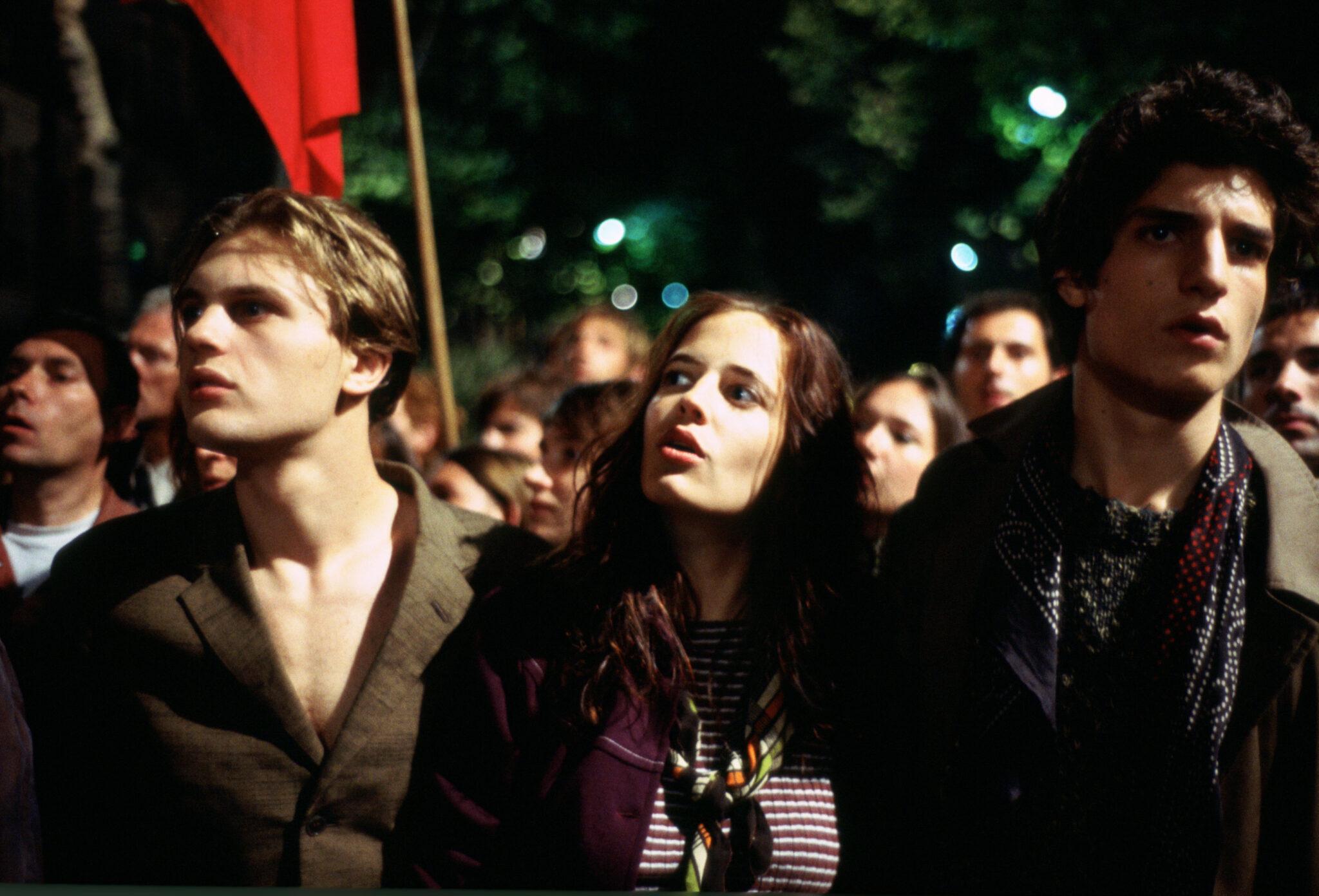 Matthew (Michael Pitt), Isabelle (Eva Green) und Theo (Louis Garrel) stehen in Die Träumer inmitten von Protestierenden auf der Straße.
