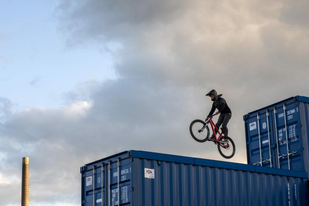 Johnny fährt hoch oben mit dem BMX Rad über Container