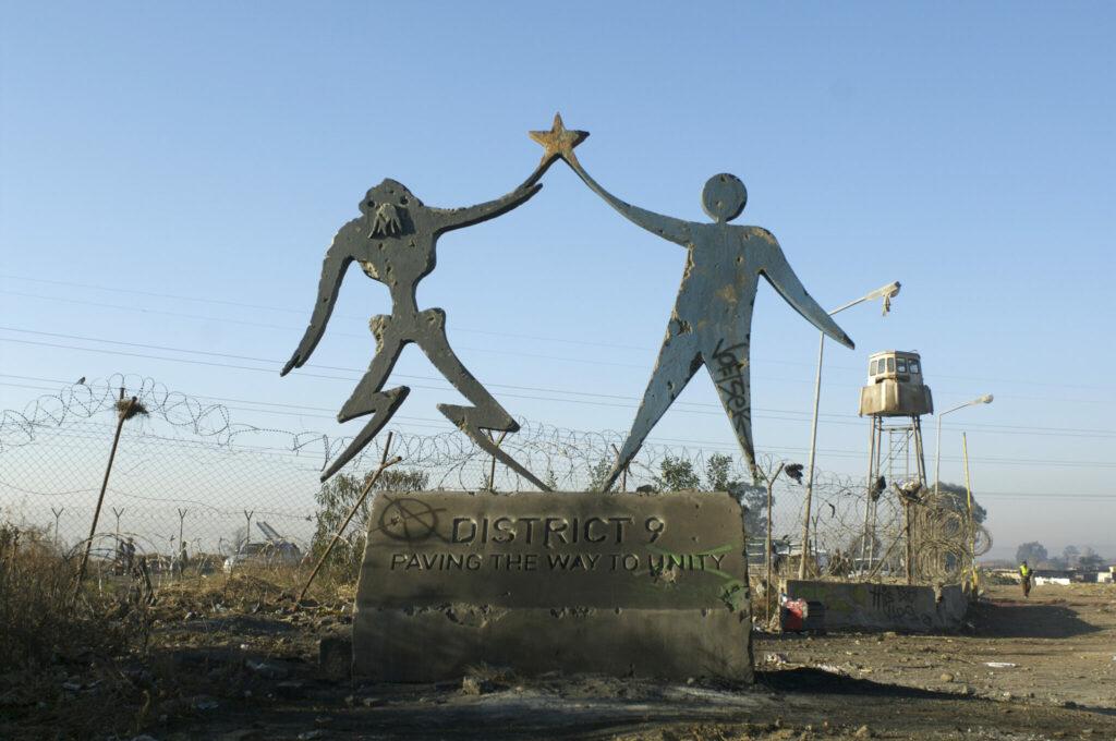 Ein verwüstetes Denkmal zeigt Aliens und Menschen in Einigkeit