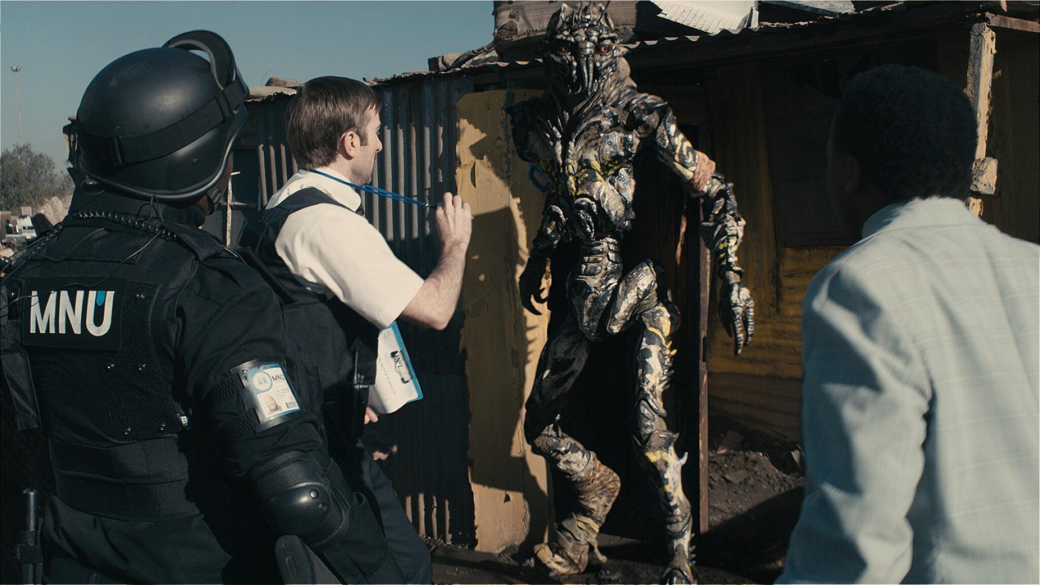 Wikus van der Merwe weist sich gegenüber einem Alien aus