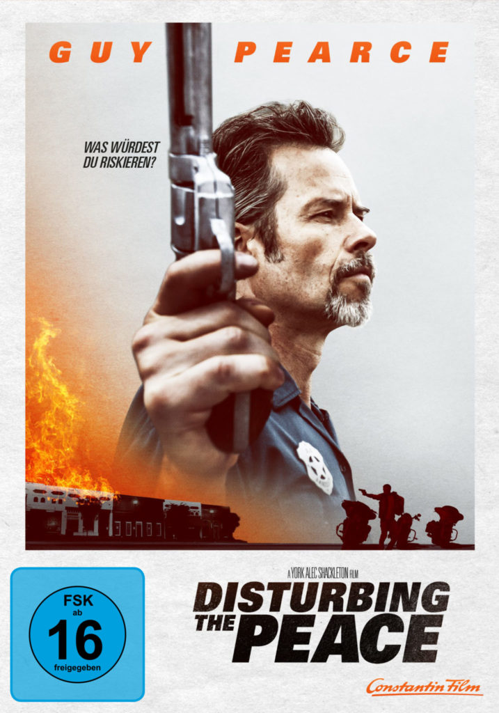Das deutsche Filmcover zu Disturbing the Peace zeigt Hauptdarsteller Guy Pearce von der Seite. Dieser hält in seiner rechten Hand einen Revolver. Links unten im Bild brennen Gebäude, rechts unten erkennt man die Silhouette von drei Motorrädern und jemanden mit Waffe.