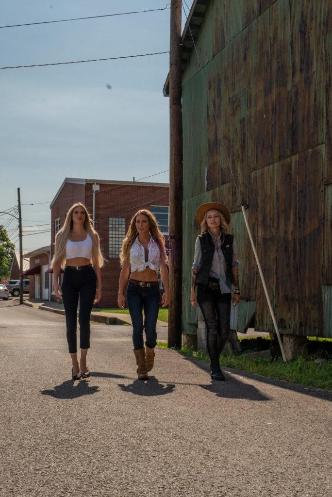 Auf dem Bild sind drei blonde Damen zu erkennen. Unter anderem die Darstellerinnen Barbie Blank und Kelly Greyson. Diese gehen nebeneinander her. Zwei der Damen tragen eine weißes bauchfreies Oberteil. Die Dritte trägt ein Jeans-Hemd, eine schwarze Lederweste und einen braunen Cowboyhut.