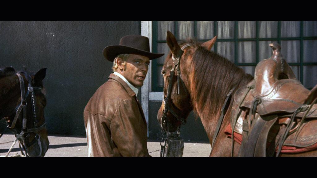 Django, gespielt von George Ardisson, steht in Django - den Colt an der Kehle neben seinem Pferd und blickt auf die andere Straßenseite.