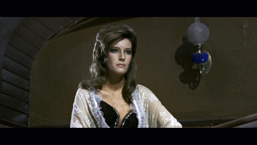 Dick Smarts Freundin, gespielt von Lilli Lembo, eine Hure, steht auf der Treppe des Saloons.