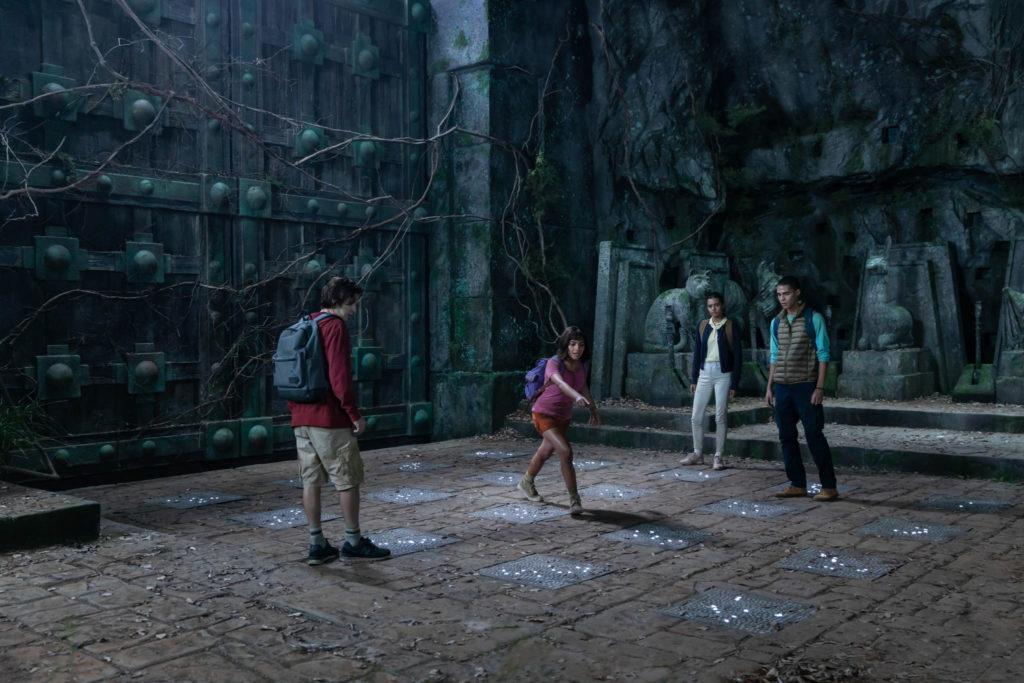 Dora und ihre Freunde stehen vor einem großen Tor auf leuchtenden Steinplatten. Dora zeigt auf eine der Platten. Dora und die goldene Stadt ©Paramount Pictures