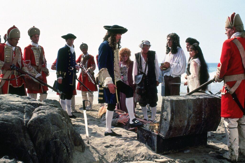 Dotterbart liegt bewusstlos im Sand, während Clement, im Rücken seine Soldaten, den Schatz für sich beansprucht, während die Gefolgschaft des Piraten resigniert dreinschaut