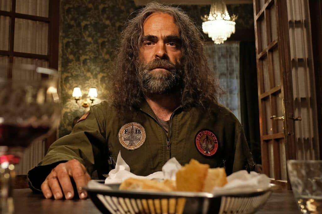 Martin sitzt verwahrlost und verstört am Esstisch vor seinem Abendessen in Die obskuren Geschichten eines Zugreisenden
