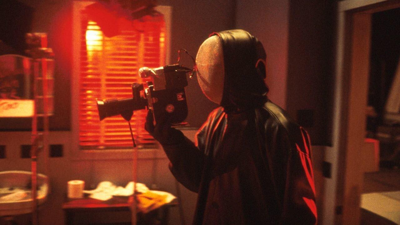 Der maskierte Killer aus Duestere Legenden 2 hält, im Profil gesehen, eine Kamera.