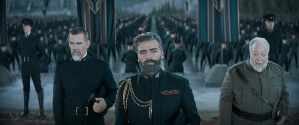 Leto Atreides (Oscar Isaac) mit seinem Vertrauten Gurney Halleck (Josh Brolin) auf einer feierlichen Versammlung, in der er nachdenklich in die Kamera blickt.