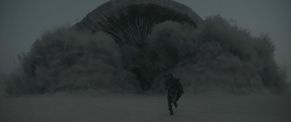 Der berühmte Sandwurm bricht hier aus dem Wüstenboden aus und schlägt Paul Atreides (Timothée Chalamet) in die Flucht in Dune (2021)