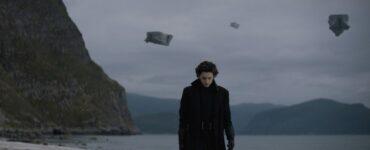 Auf dem Bild sieht man Timothée Chalamet als Paul Atreides, der an einem Strand entlanggeht. Das Bild sieht sehr trist aus. Im Hintergrund ist eine kleine Felsformation zu sehen. Des Weiteren scheinen Gegenstände in der Luft zu schweben.