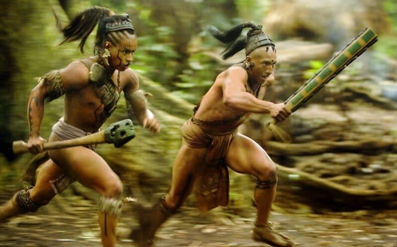 Zwei Eingeborene rennen in traditioneller Kleidung und mit gezückten Waffen durch den Wald, sie sehen angespannt und wütend aus
