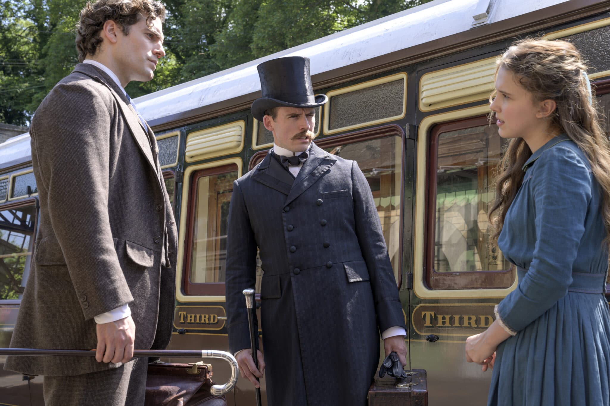 Enola steht mit ihren zwei Brüdern vor einem Zug, alle drei haben einen unsicheren Blick, Sherlock und Mycroft tragen Gehstöcke und Koffer in ihren Händen