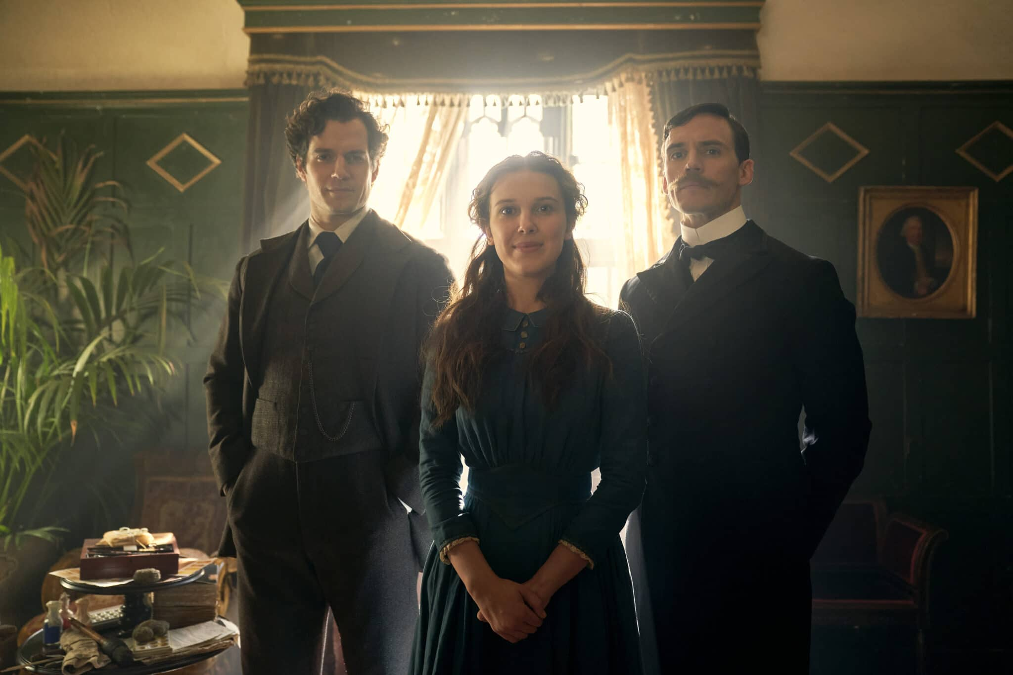 Enola steht auf einem Familienfoto lächelnd zwischen Sherlock und Mycroft in einem geräumigen, alten Zimmer, im Hintergrund scheint Licht durchs Fenster, an der Seite steht eine Pflanze und ein Tisch mit diversem Zeug drauf