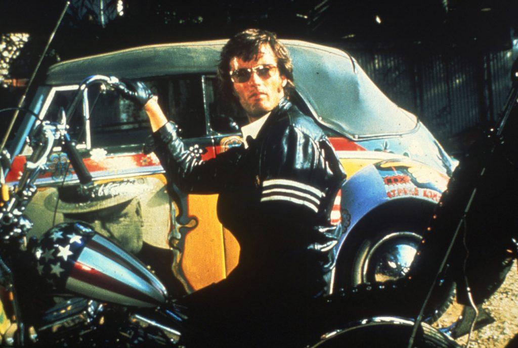 Peter Fonda in Bikerklamotten sitzt auf einem Motorrad in Easy Rider