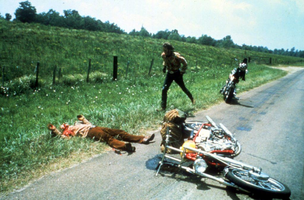 Peter Fonda läuft auf den verletzt am Boden liegenden Dennis Hopper zu, dessen beschädigtes Motorrad neben ihm auf der Straße liegt