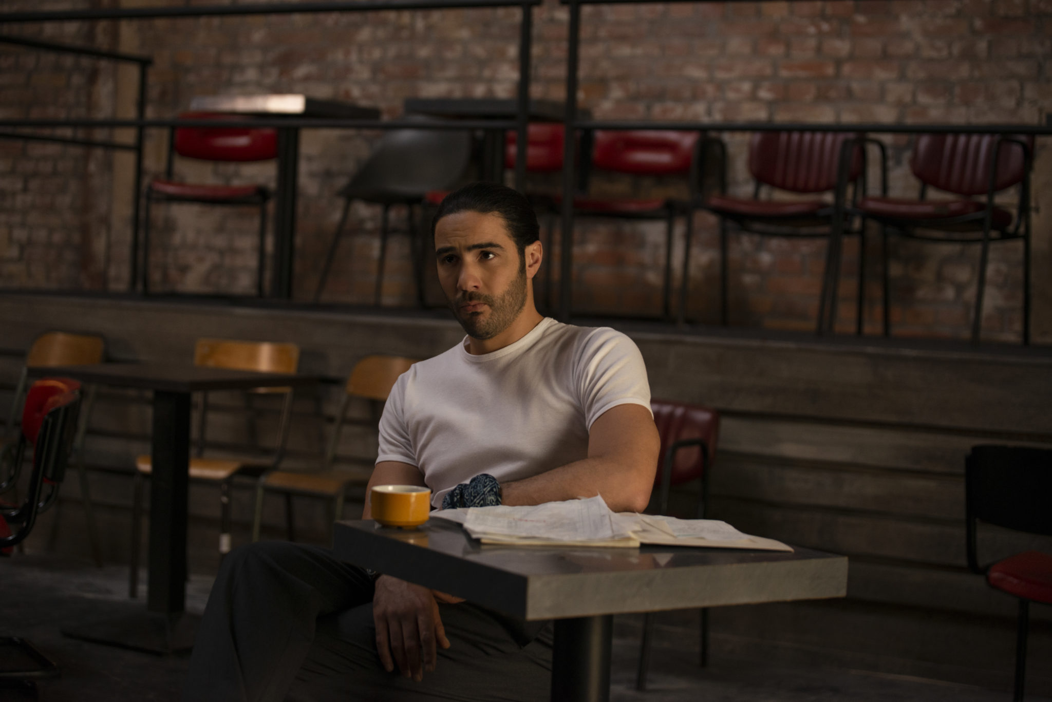 Farid sitzt in The Eddy alleine an einem Tisch im verlassenen Jazzclub, im Hintergrund leere Sitzreihen, auf dem Tisch eine Tasse und diverse Papiere