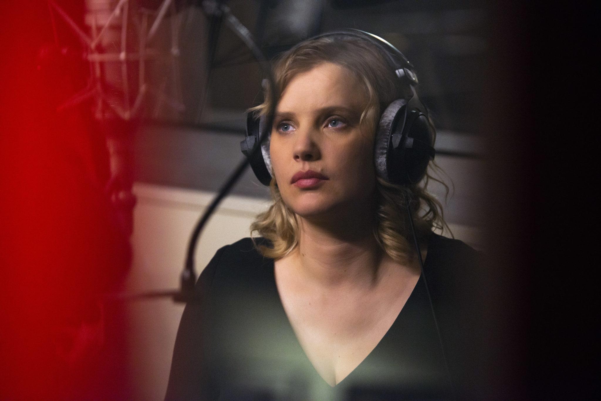 Maja im Musikstudio in The Eddy, auf dem Kopf große Kopfhörer, vor ihr das Mikro für die Aufnahme