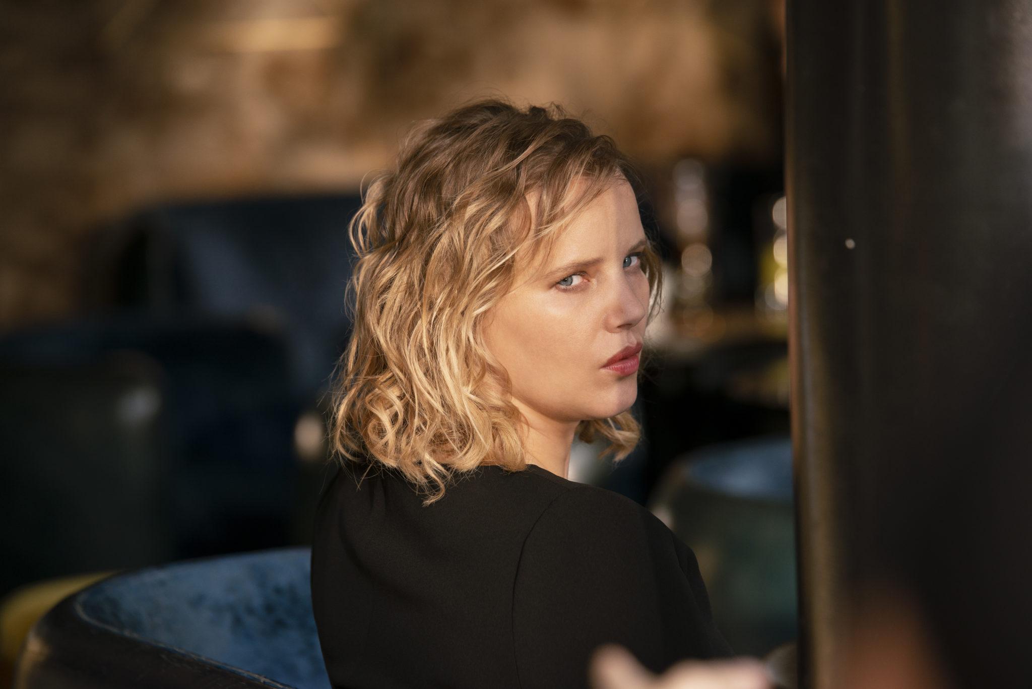 Maja, gespielt von Joanna Kulig, dreht sich in Nahaufnahme in The Eddy in die Kamera, im Hintergrund verschwommen eine Sitzecke