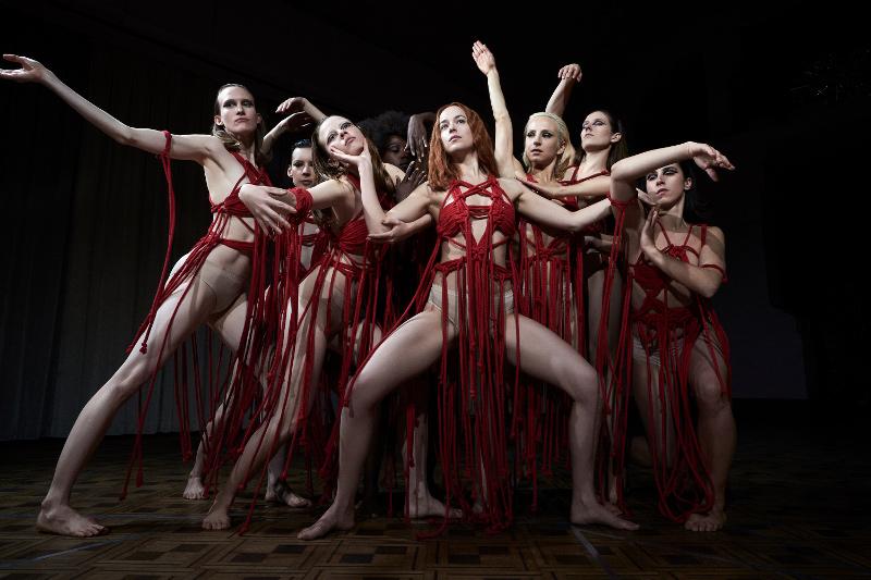 Die Tänzerinnen posieren, bekleidet mit knappen roten Bikinis, an denen rote Bänder hängen, in einer Tanzpose