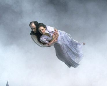 """Ein Paar schwebt fest umschlungen über einer zerstörten Stadt in """"Über die Unendlichkeit"""""""