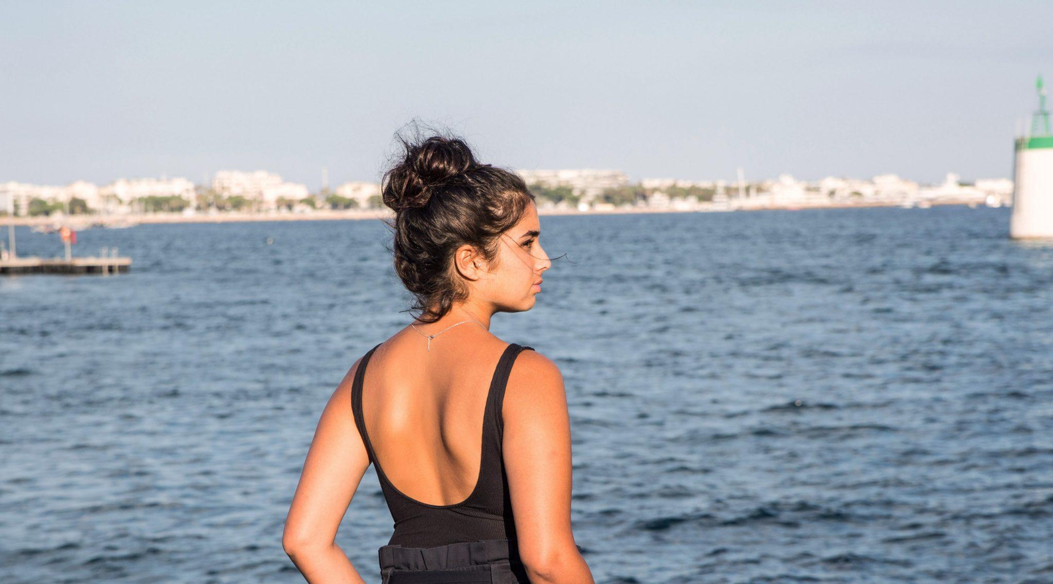 Naïma steht in der Sonne am Strand von Cannes, im Hintergrund ist das Meer zu sehen.