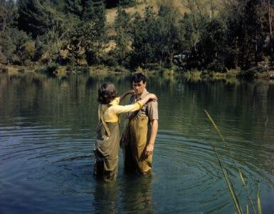 Abigail, gespielt von Paula Prentiss, und Roger, gespielt von Rock Hudson, stehen sich dicht gegenüber knietief im Wasser. Beide tragen Angelhosen, Abigail hat ihre Arme auf Rogers Schultern gelegt.