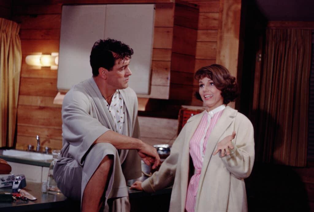 Abigail, gespielt von Paula Prentiss, und Roger, gespielt von Rock Hudson, stehen in Pyjamas nebeneinander in Rogers Bungalow und unterhalten sich.