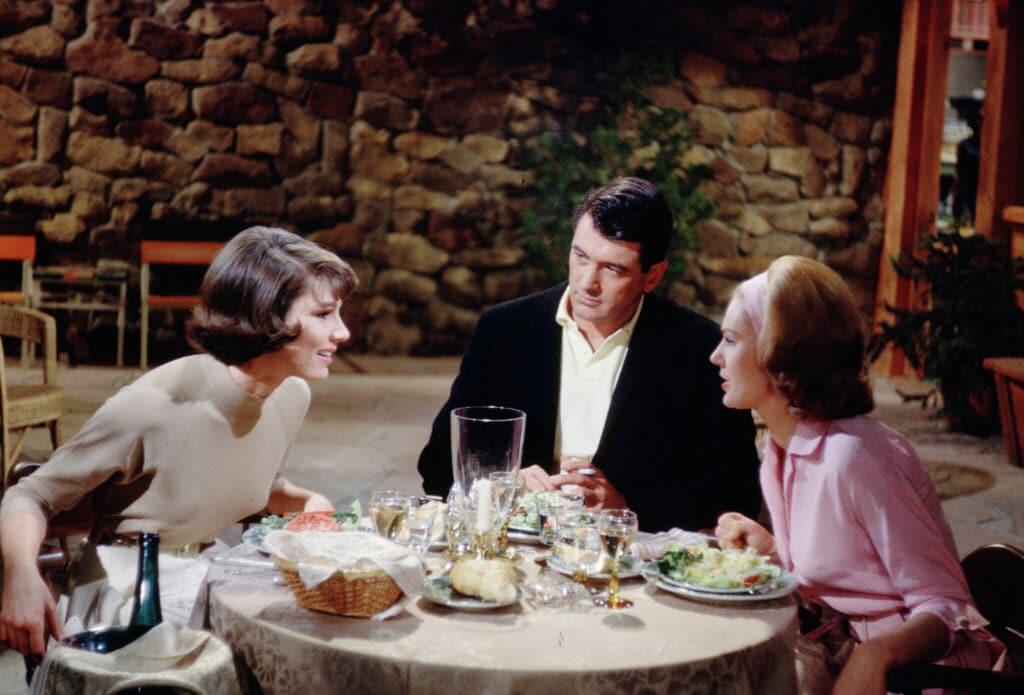 Abigail, gespielt von Paula Prentiss, Roger, gespielt von Rock Hudson, und Easy, gespielt von Maria Perschy, sitzen in Ein Goldfisch an der Leine gemeinsam an einem mit Essen beladenen Tisch.