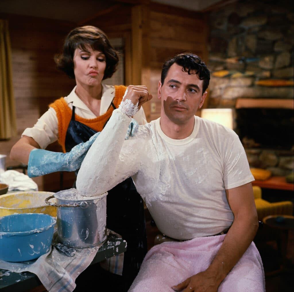 Abigail, gespielt von Paula Prentiss, gipst den Arm von Roger, gespielt von Rock Hudson, ein.