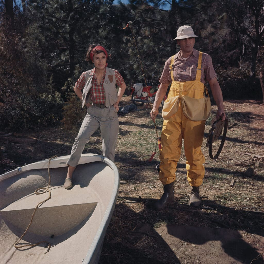 Abigail, gespielt von Paula Prentiss, und Roger, gespielt von Rock Hudson, stehen in Ein Goldfisch an der Leine gemeinsam vor einem Ruderboot, Abigail ist mit einem Bein bereits hineingetreten.