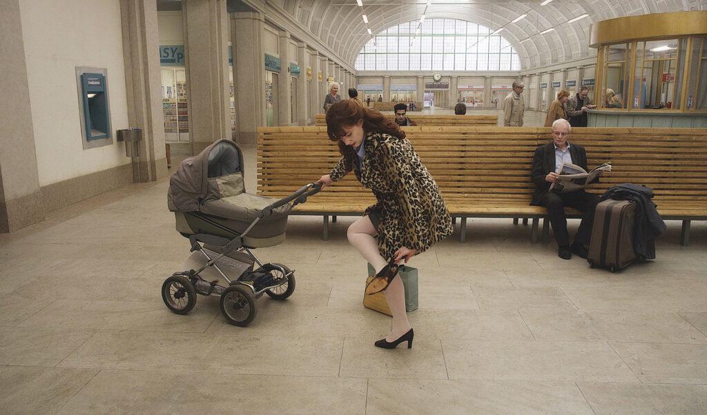Eine Frau mit Kinderwagen hat ein Problem mit ihrem Schuh in Über die Unendlichkeit, im Hintergrund diverse Leute mit Gepäck.