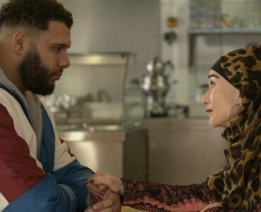 Patience, gespielt von Isabelle Huppert, sitzt mit ihrem Straßendealer Scotch (Rachid Guellaz) an einem Tisch in einem Bistro.
