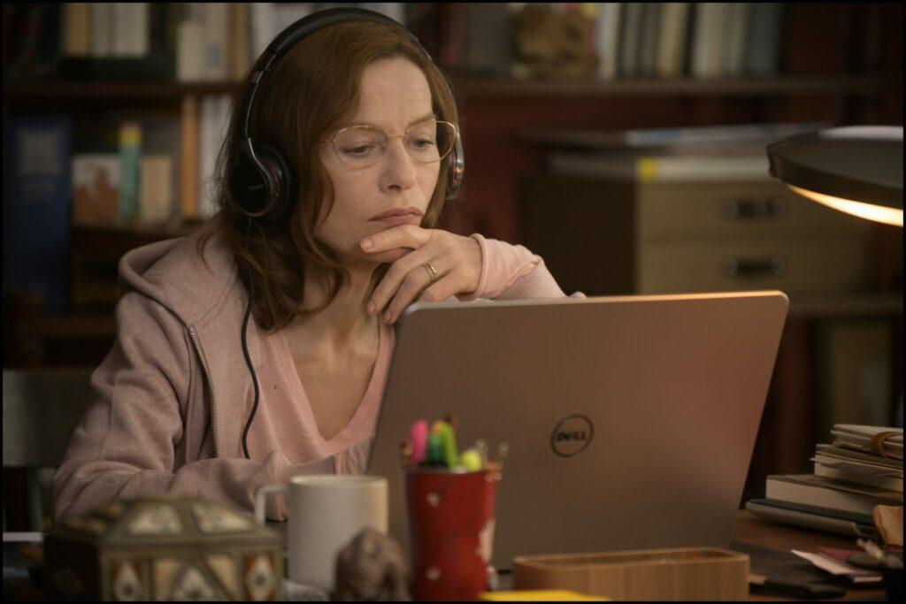 Patience, gespielt von Isabelle Huppert, sitzt in Eine Frau mit berauschenden Talenten zu Hause am PC und hört die Gespräche der Dealer ab.
