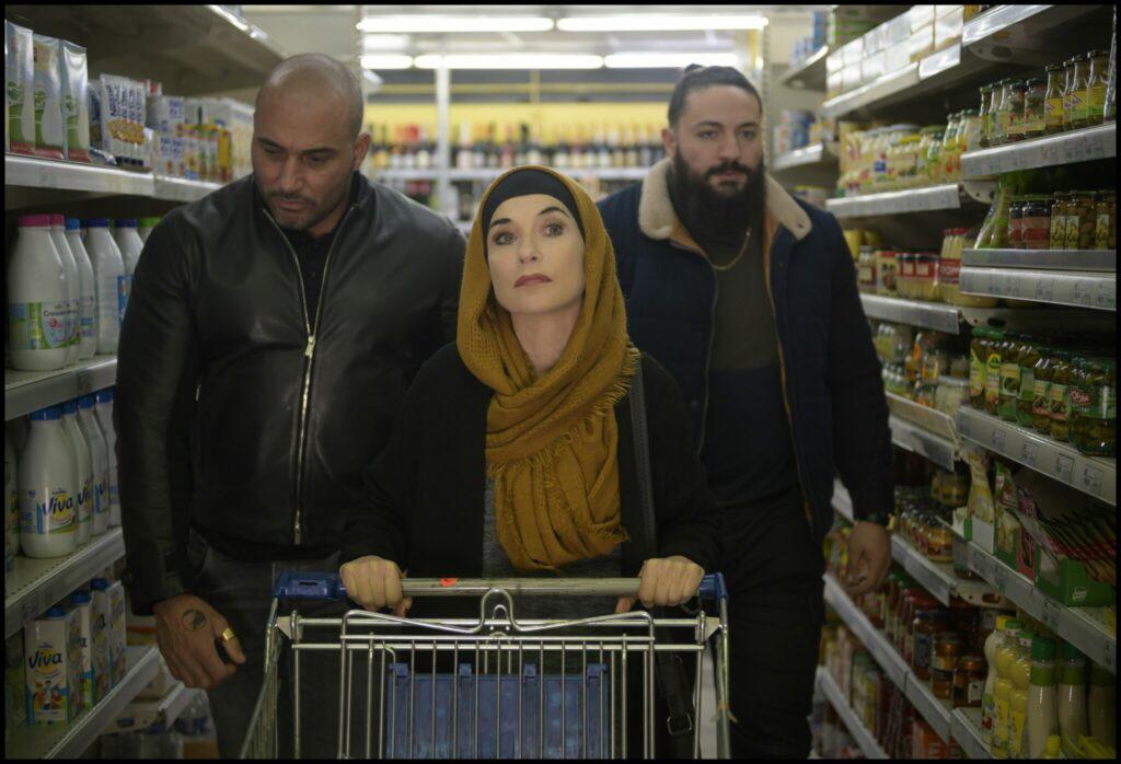 Patience, gespielt von Isabelle Huppert, schiebt einen Einjaufswagen durch einen Supermarkt. Hinter ihr gehen ihre Straßendealer Scotch, gespielt von Rachid Guellaz, und Chocapic, gespielt von Mourad Boudaoud.