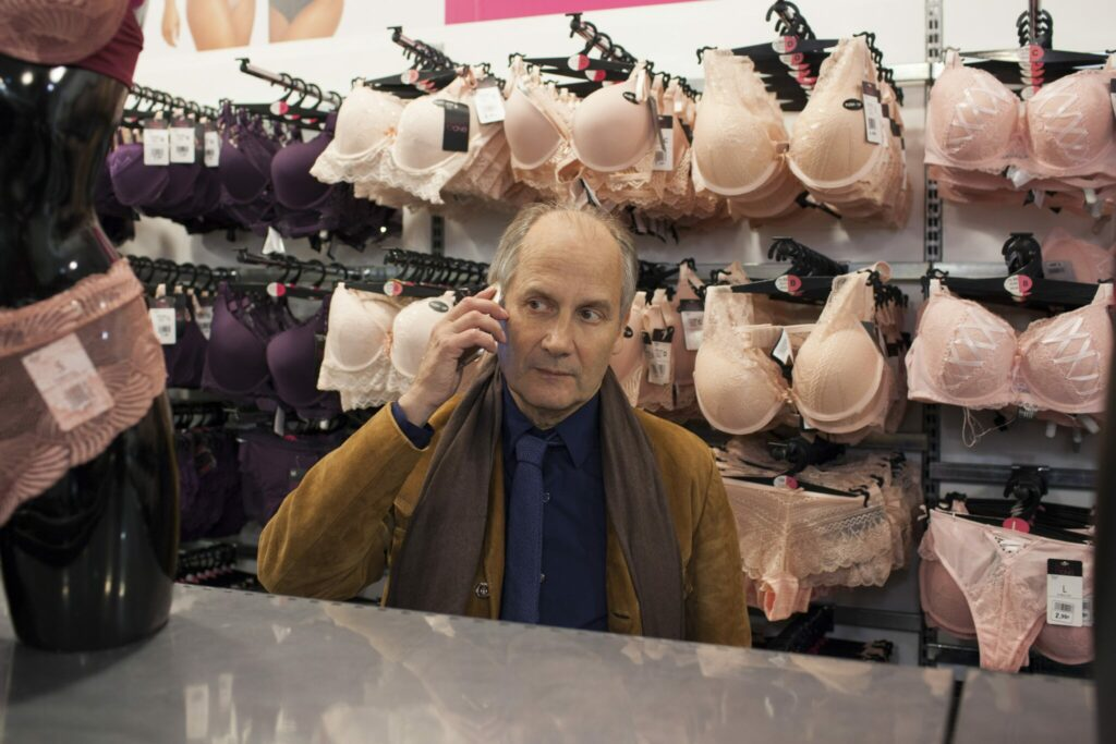 Philippe, gespielt von Hippolyte Girardot, steht in der Dessouabteilung eines Kaufhauses und telefoniert mit dem Handy.