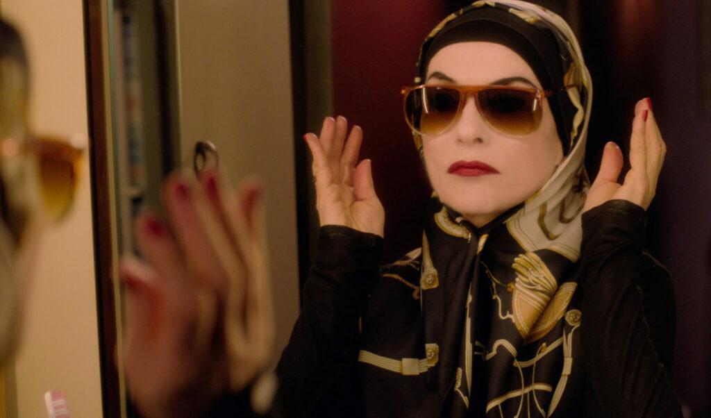 Patience, gespielt von Isabelle Huppert, prüft in Eine Frau mit berauschenden Talenten vorm Spiegel ihre Maske als Madame Hasch. Sie trägt Hijab, dicke Schminke und eine große Sonenbrille.