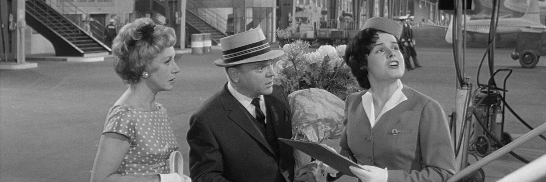 MacNamara (James Cagney) steht in Eins, zwei, drei mit seiner Frau und Blumenstrauß in der Hand am Flughafen.