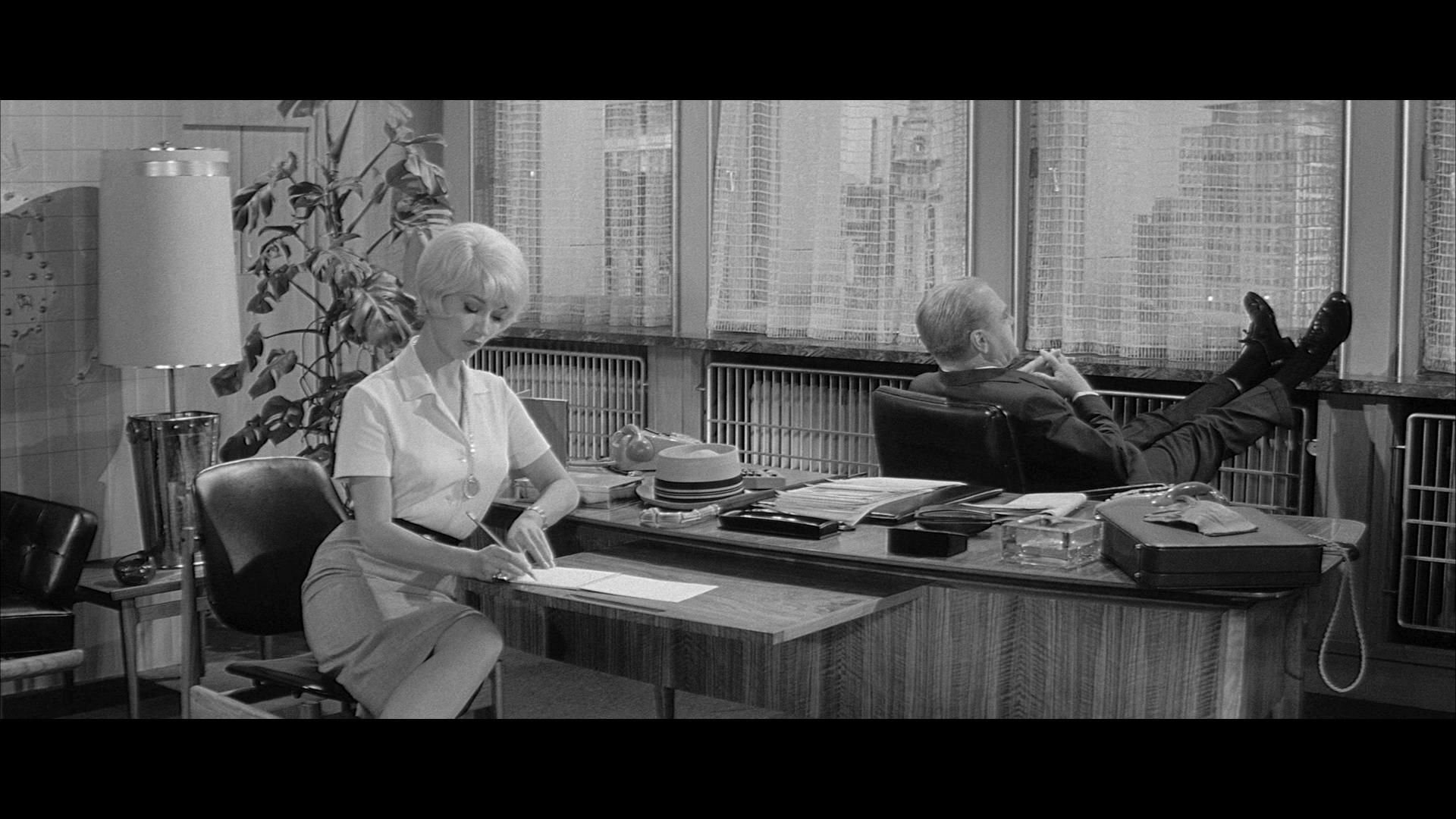 MacNamara (James Cagney) sitzt in Eins, zwei, drei in seinem Bürostuhl, die Füße hochgelegt auf das Fensterbrett. Fräulein Ingeborg hört zu und macht Notizen.