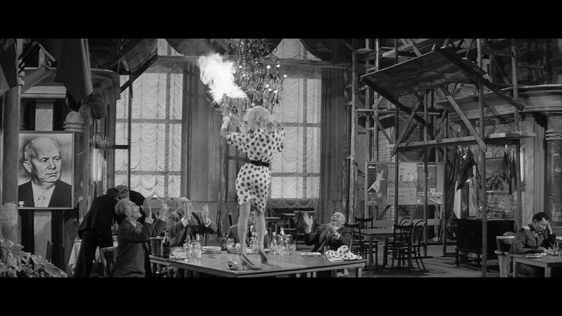 Fräulein Ingeborg (Liselotte Pulver) tanzt in Eins, zwei, drei ausgelassen auf einem Tisch, die drei Sowjets geben aufgeregt Beifall.