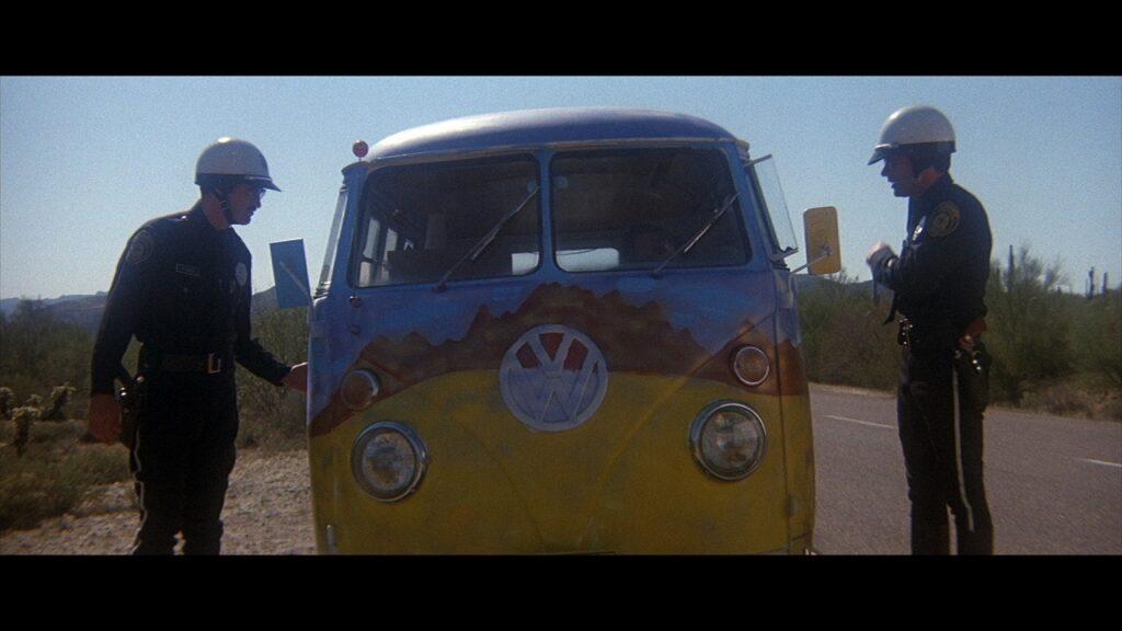 Die Highway-Cops John und Zipper kontrollieren einen bunt angemalten VW-Bus, einer links, einer rechts vom Gefährt, das frontal gezeigt wird - Electra Glide in Blue