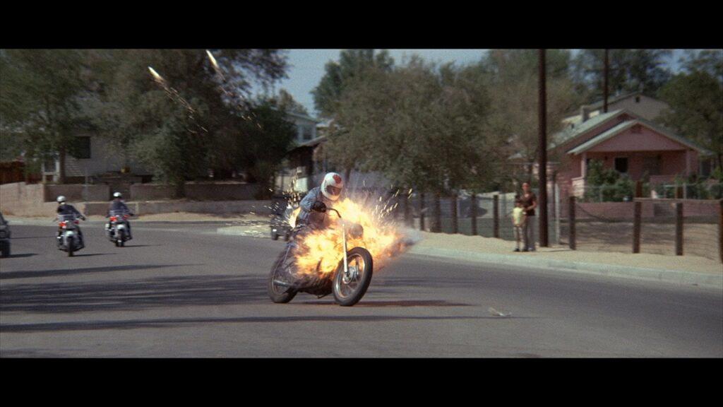 Ein Motorad, dass die beiden Cops durch eine Ortschaft verfolgen geht während der Fahrt in Flammen auf - Electra Glide in Blue